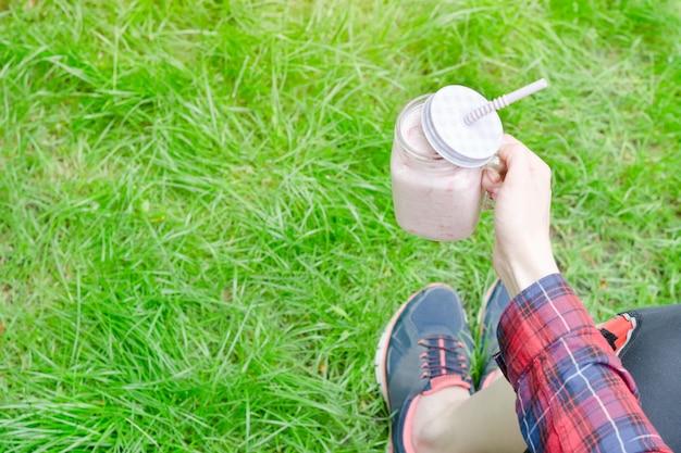 Aardbei smoothies in vrouwelijke hand op een achtergrond van groen gras Premium Foto