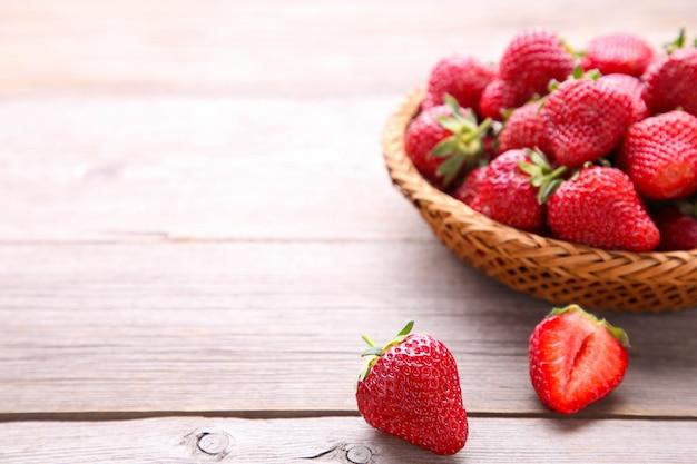 Aardbeien in de mand op grijs hout Premium Foto