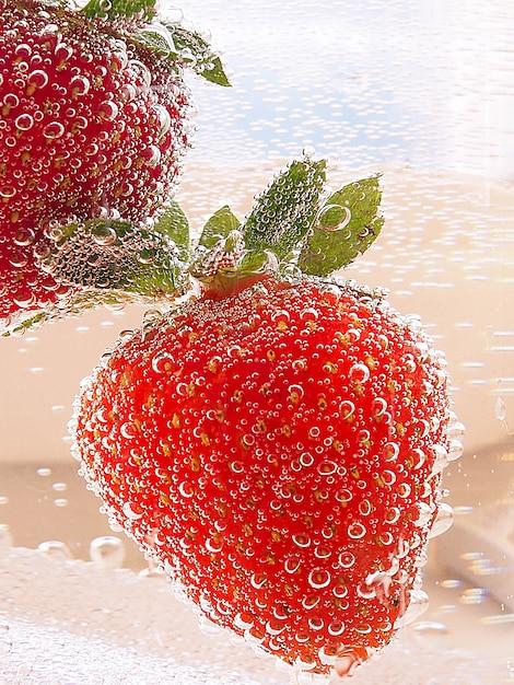 Aardbeien in een glazen container met bubbels in neon toning met verloop Premium Foto