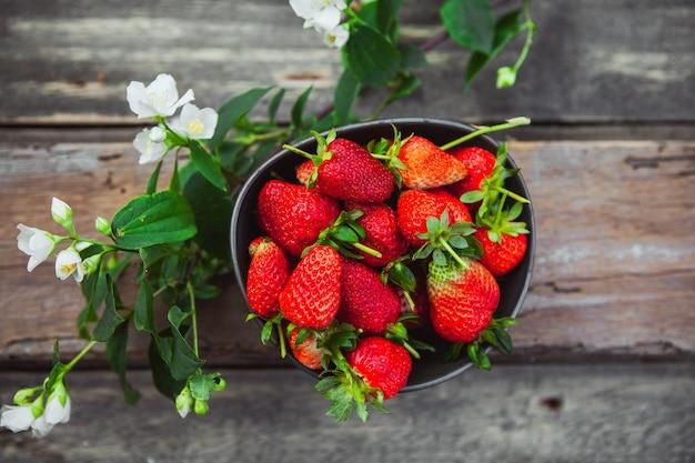 Aardbeien in een kom met bloem tak bovenaanzicht op oude houten tafel Gratis Foto
