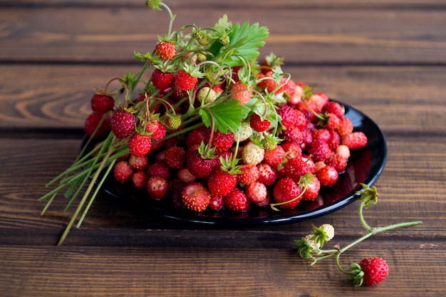 Aardbeien in een witte mok op een rustieke houten tafel. het concept van biologisch voedsel. rustieke stijl Premium Foto