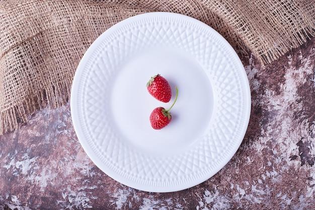 Aardbeien in een witte plaat, bovenaanzicht. Gratis Foto