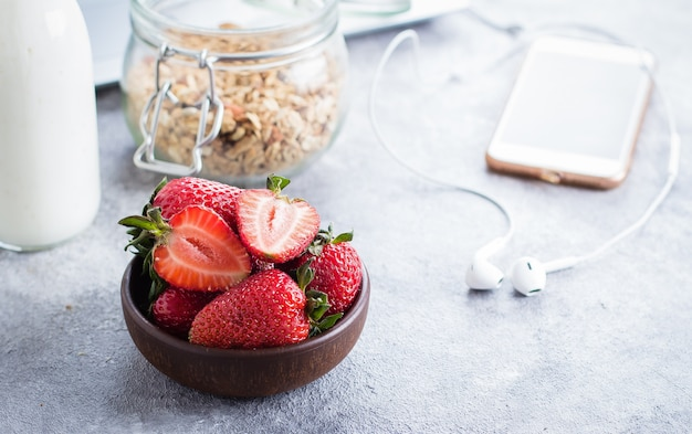 Aardbeien, yoghurt fles en granola pot, laptop en koptelefoon op lichte stenen tafel achtergrond. Premium Foto