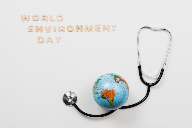 Aarde over stethoscoop en tekstwereld milieudag Gratis Foto