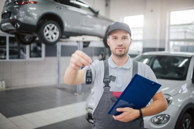 Aardige en zelfverzekerde man staat en kijkt op camera. hij heeft autosleutels en een plastic map met documenten. er staan sleepauto's achter hem. Premium Foto