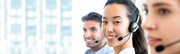 Aasianvrouw die in call centre op bannerachtergrond werken Premium Foto