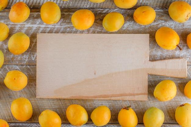 Abrikozen plat lag op houten en snijplank Gratis Foto