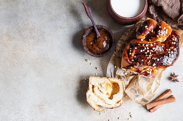 Abrikozenjam gedraaid brood of babka met noten en kruiden met een kopje melk. Premium Foto
