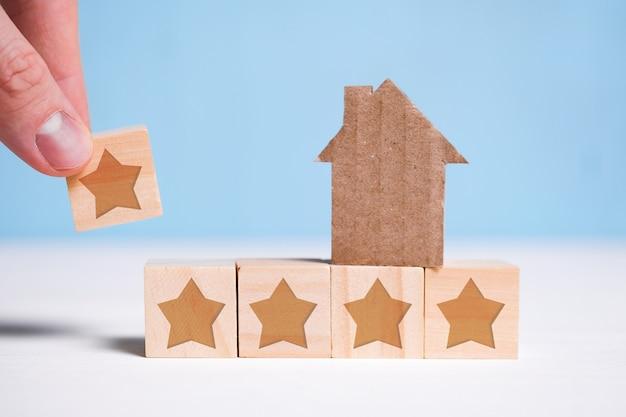 Abstract huis gemaakt van karton. hand zet een kubus met een ster op een blauw. hoogste cijfer. woningwaardering. Premium Foto