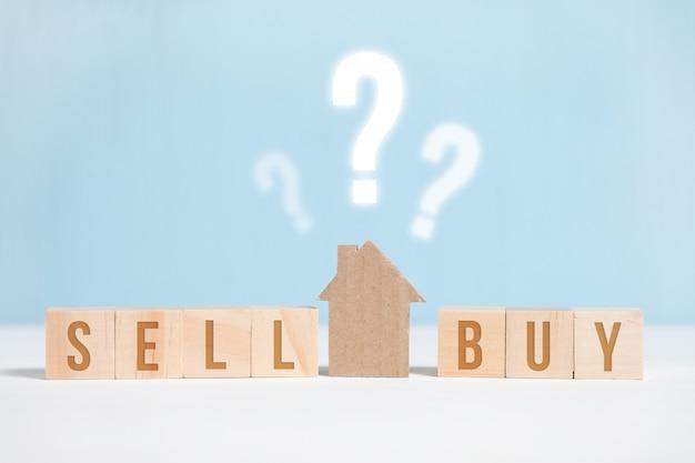 Abstract huis gemaakt van karton op een blauwe achtergrond met de inscriptie. Premium Foto