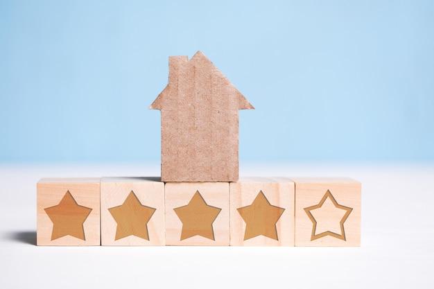 Abstract kartonhuis op houten kubussen met sterren op een blauw. woningclassificatie. Premium Foto