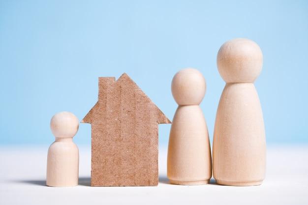 Abstract kartonnen huis in de buurt van het gezin: moeder, vader, baby. huiseigendom. Premium Foto