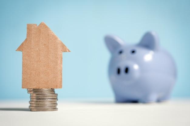 Abstract kartonnen huis op een stapel munten naast een spaarvarken Premium Foto