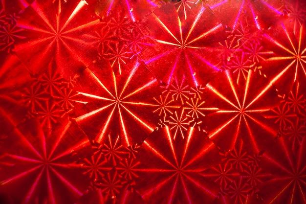 Abstract patroon met stralen op rood holografisch papier. Premium Foto