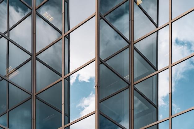 Abstracte achtergrond van wolken weerspiegeld op de glazen hoeken van een kantoorgebouw Premium Foto