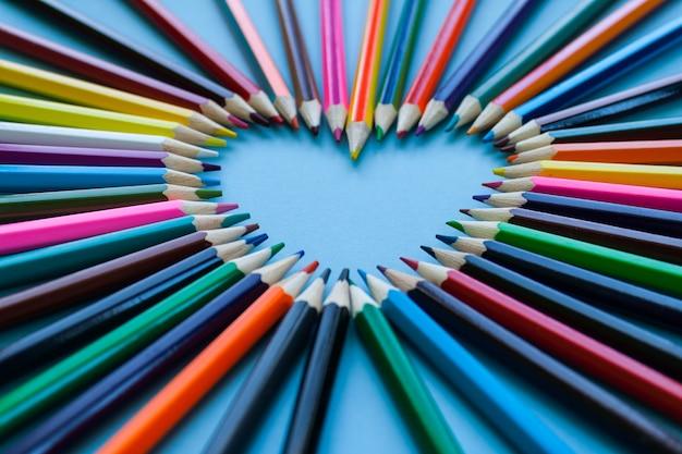 Abstracte achtergrond wazig. kleurpotloodhart - hartvorm gemaakt van kleurpotloden Premium Foto