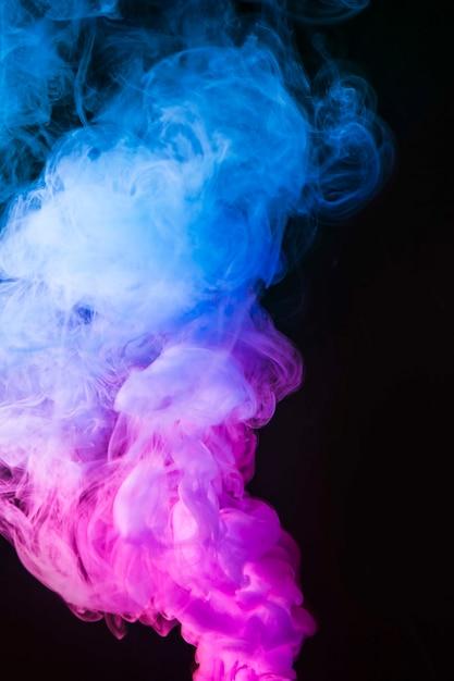 Abstracte blauwe en roze rookbeweging op zwarte kleurenachtergrond Gratis Foto