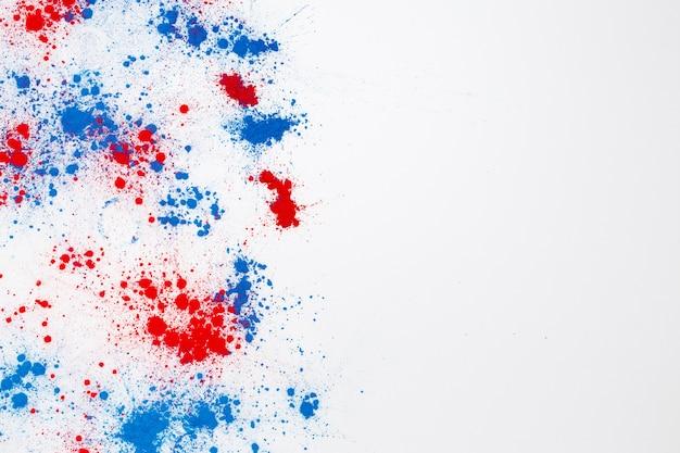 Abstracte explosie van rode en blauwe holi kleur poeder met copyspace aan de rechterkant Gratis Foto