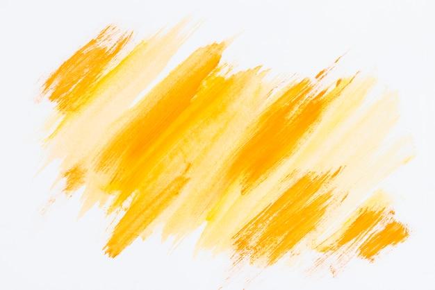 Abstracte gele penseelstreek op witte achtergrond Gratis Foto
