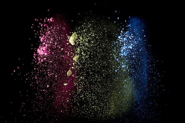 Abstracte kleurrijke stofdeeltjes gestructureerde achtergrond. veelkleurige poeder explosie op zwarte achtergrond. Premium Foto