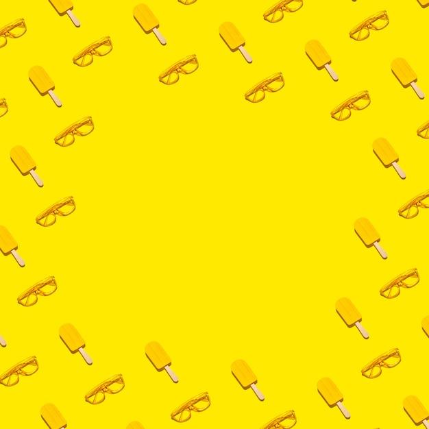 Abstracte minimale zomer plat lag grenskader van gele ijslollys en zonnebril op abstracte levendige achtergrond met kopie ruimte Premium Foto