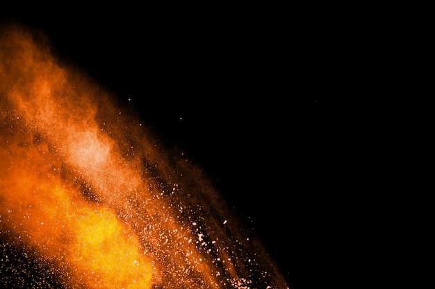 Abstracte oranje poederexplosie op zwarte achtergrond Premium Foto