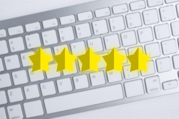 Abstracte vijf sterren over wazig toetsenbord met de beste beoordeling. uitstekend cijfer. beste score. plat leggen. Premium Foto