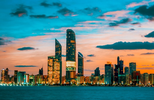 Abu dhabi skyline bij zonsondergang, verenigde arabische emiraten Premium Foto