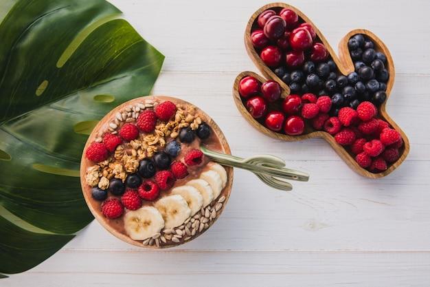 Acai smoothie, muesli, zaden, vers fruit in een houten kom met cactuslepel. plaat gevuld met bessen Premium Foto