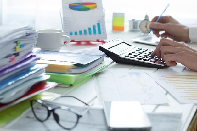 Accountant op een rekenmachine die een financieel rapport. fiscale tijd. Premium Foto