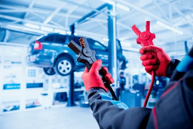 Accumulator opladen. handen en terminals. auto reparatie. Premium Foto