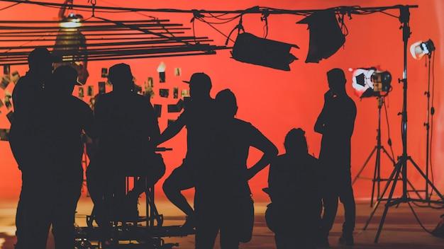 Achter de schermen met cameraman die een videofilm filmt terwijl het productieteam het podium opzet Premium Foto