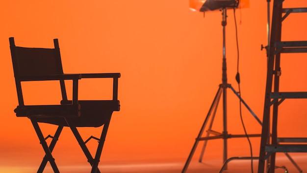 Achter de schermen met regisseursstoel videofilm filmen met productieteam dat het podium opzet Premium Foto
