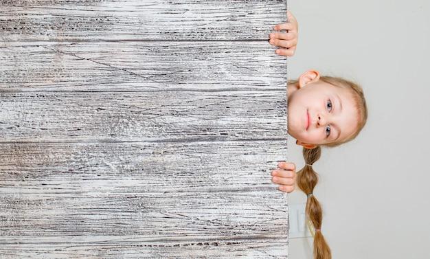 Achter houten plank verbergen en meisje die zorgvuldig kijken. . Gratis Foto