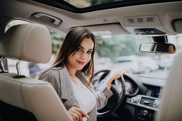 Achter mening van een aantrekkelijke jonge bedrijfsvrouw die over haar schouder kijkt tijdens het besturen van een auto Gratis Foto