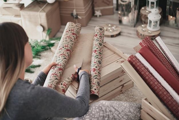 Achter mening van vrouw die een kerstmisdocument snijdt Gratis Foto