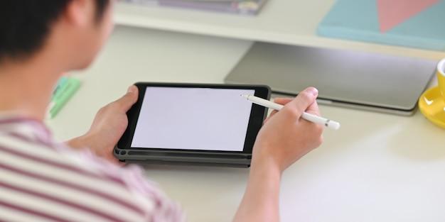 Achter schot van jonge creatieve man puttend uit witte leeg scherm computertablet door stylus pen. Premium Foto