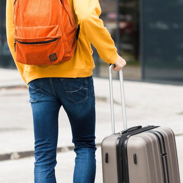 Achteraanzicht alleen reiziger met bagage Gratis Foto