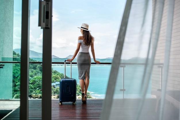 Achteraanzicht: een mooie toerist met een luxe figuur in een hoed poseert met haar bagagebalkon, dat een prachtig uitzicht op de zee en de bergen biedt. reizen en vakantie. Premium Foto