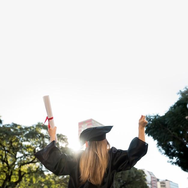Achteraanzicht enthousiast meisje zijn afstuderen Gratis Foto