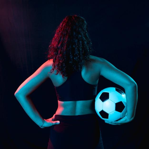 Achteraanzicht fit jong meisje met voetbal Gratis Foto