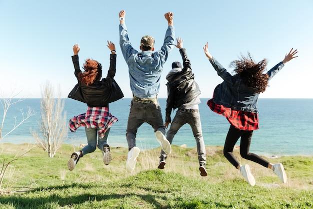 Achteraanzicht foto van een groep vrienden springen Gratis Foto