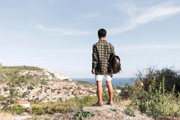 Achteraanzicht jonge man genieten van landschap Gratis Foto
