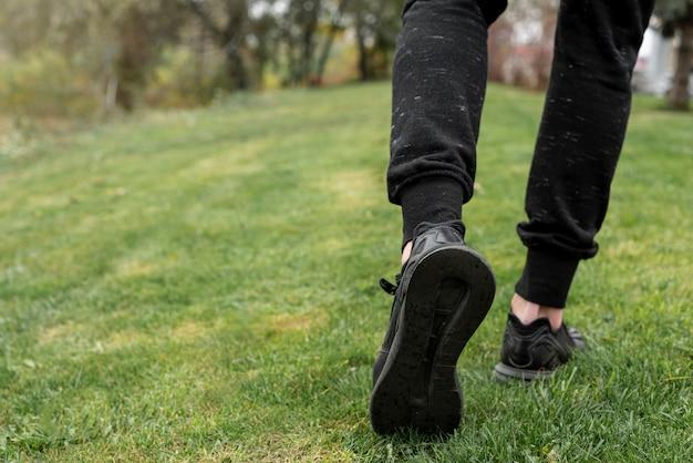 Achteraanzicht man benen lopen op gras Gratis Foto