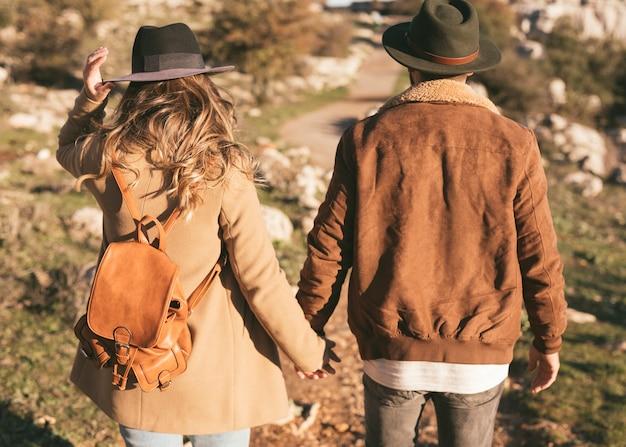 Achteraanzicht man en vrouw hand in hand buiten Gratis Foto