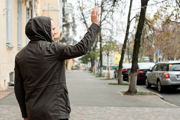 Achteraanzicht man lopen op straat en groeten Gratis Foto