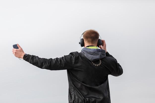 Achteraanzicht man luisteren naar muziek buiten Gratis Foto
