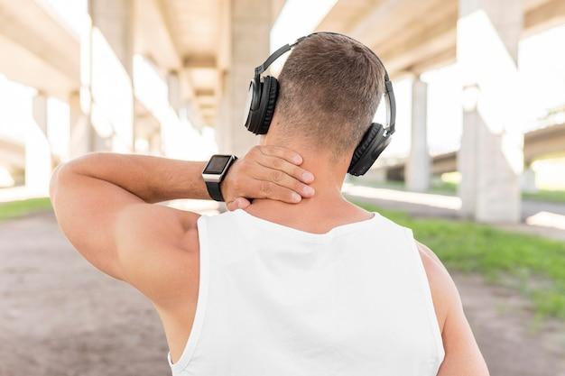 Achteraanzicht man luisteren naar muziek via de koptelefoon alvorens te trainen Gratis Foto