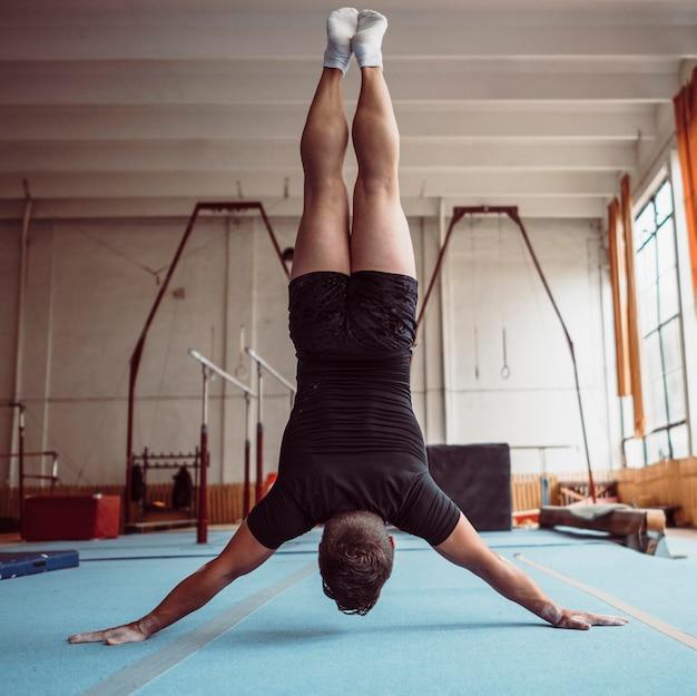 Achteraanzicht man training met parallelle staven Gratis Foto