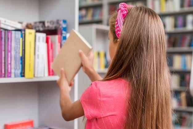 Achteraanzicht meisje een boek terug op de plank te zetten Gratis Foto
